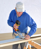 Carpenter cutting siding with shears. Carpenter cutting fibrous cement siding with power shears royalty free stock photo