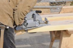 Carpenter cutting steps with saw Stock Image