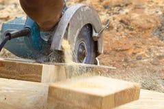 Carpenter Cutting Wood. A carpenter cutting wood using a circular saw Royalty Free Stock Images