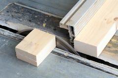 Carpenter cutting wood on electric saw Stock Photos