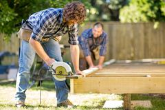 Carpenter Cutting Wood With Handheld Saw While Royalty Free Stock Photos