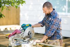 Carpenter Cutting Wood Using Table Saw At Stock Images