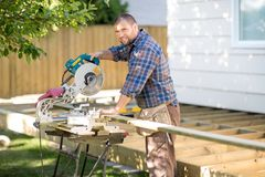 Carpenter Cutting Wood Using Table Saw At Site Stock Photo