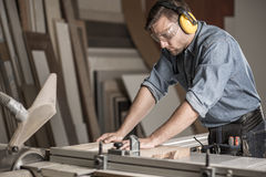 Carpenter cutting wood on workbench royalty free stock photography