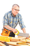 Carpenter cutting wooden batten with a saw. On white background stock photo