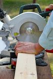 Carpenter cutting wooden plank with circular saw Royalty Free Stock Photo