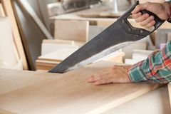 Carpenter Cutting Wooden Plank With Handsaw Stock Image