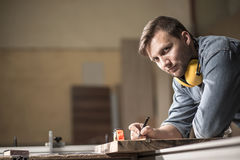 Carpenter designing wooden furniture. Handsome bearded hardworking carpenter designing wooden furniture Stock Photo