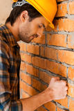 Carpenter in despair. Side view of depressed young man in hardhat leaning at the brick wall and keeping eyes closed Stock Images