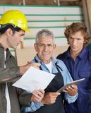Carpenter Discussing With Colleagues In Workshop Royalty Free Stock Images