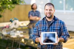 Carpenter Displaying Digital Tablet With Coworker. Portrait of mid adult carpenter displaying digital tablet with coworker in background at construction site stock images