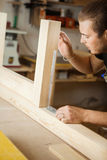 Carpenter does measurements according to project. Woodworker workshop Royalty Free Stock Image