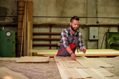 Carpenter doing his job in carpentry workshop Royalty Free Stock Image