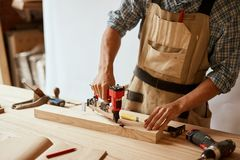 Carpenter drills a hole with an electrical drill royalty free stock images