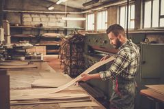 Carpenter doing his work in carpentry workshop. Royalty Free Stock Photos