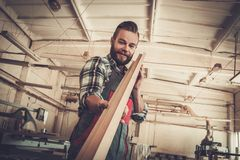Carpenter doing his work in carpentry workshop. Stock Photo