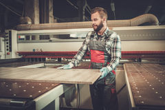 Carpenter doing his work in carpentry workshop. Royalty Free Stock Image
