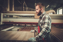 Carpenter doing his work in carpentry workshop. Stock Image