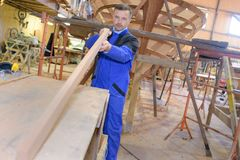 Carpenter doing job in carpentry workshop royalty free stock photos