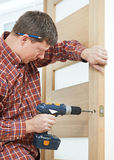 Carpenter at door lock installation. Male handyman carpenter at interior wood door lock installation stock photos