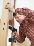 Carpenter at door lock installation. Male handyman carpenter at interior wood door lock installation stock photo