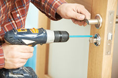 Carpenter at door lock installation Royalty Free Stock Images