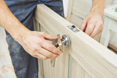 Carpenter at door lock installation. Male handyman carpenter at interior wood door lock installation royalty free stock photo