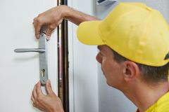 Carpenter at door lock installation Royalty Free Stock Image
