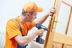 Carpenter at door lock installation or repair. Male handyman carpenter at interior wood door lock installation or repair Stock Photos