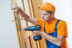 Carpenter at door lock installation or repair Royalty Free Stock Image