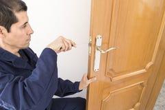 Carpenter doors. Carpenter fixing a lock in the door  with a screwdriver Stock Images
