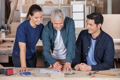 Carpenter Drawing Blueprint With Team At Table Royalty Free Stock Photography