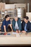 Carpenter Drawing Blueprint With Team At Workbench Stock Images