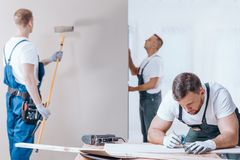 Carpenter drawing on fiberboard. Carpenter drawing on a fiberboard and painter with toolbelt painting the wall during interior finishing work stock images
