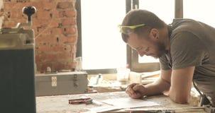Carpenter draws, close-up, in carpentry workshop. Carpenter working on a drawing, close-up, in a carpentry workshop. Man stock footage