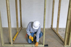 Carpenter drilling. Carpenter fixing a timber framework into a concrete floor Royalty Free Stock Images