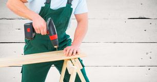 Carpenter drilling against white wood panel Royalty Free Stock Photo