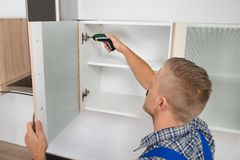 Carpenter Drilling In Cabinet Stock Photos
