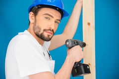 Carpenter drilling a hole in a plank of wood Royalty Free Stock Photo