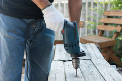 Carpenter drilling table. Carpenter use Electric drill drilling wood table royalty free stock image