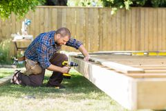 Carpenter Drilling Wood At Construction Site Stock Photo