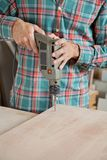 Carpenter Drilling Wood At Workbench In Workshop Royalty Free Stock Image