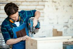 Wood boring drill in hand drilling hole in wooden bar. Carpenter drills a hole with an electrical drill Royalty Free Stock Photo