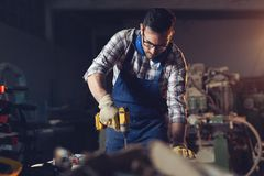 Carpenter drills a hole with an electrical drill. Young carpenter drills a hole with an electrical drill royalty free stock photography