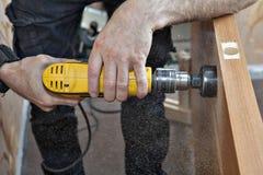 Carpenter drills  latch hole of doorlock, wood shavings flying a Royalty Free Stock Photos