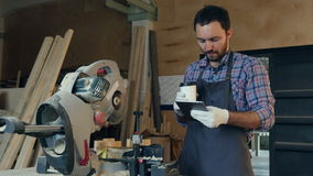 The carpenter drink coffee and using tablet in workshop near electric saw. stock video
