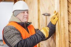 Carpenter drives a nail in board Royalty Free Stock Photo