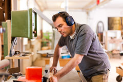Carpenter with electric cutter. Carpenter is standing on electric cutter with ear protection Royalty Free Stock Photo