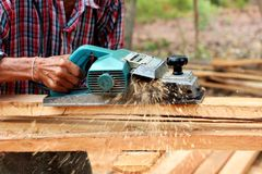 Carpenter  electric planer with wooden. Hand of carpenter using electric planer with wooden plank smooth Stock Images