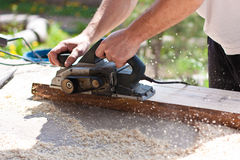 Carpenter with electric planes Royalty Free Stock Images